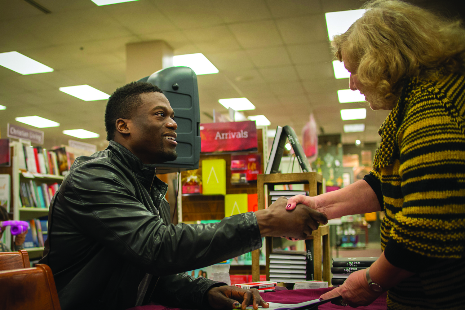 """New Orleans Saints tight end Ben Watson shakes hands with a fan before signing a copy of his new book """"Under Our Skin: Getting Real About Race -- And Getting Free from the Fears and Frustrations that Divide Us"""" that calls for racial reconciliation in Christ. Photo by Marilyn Stewart"""