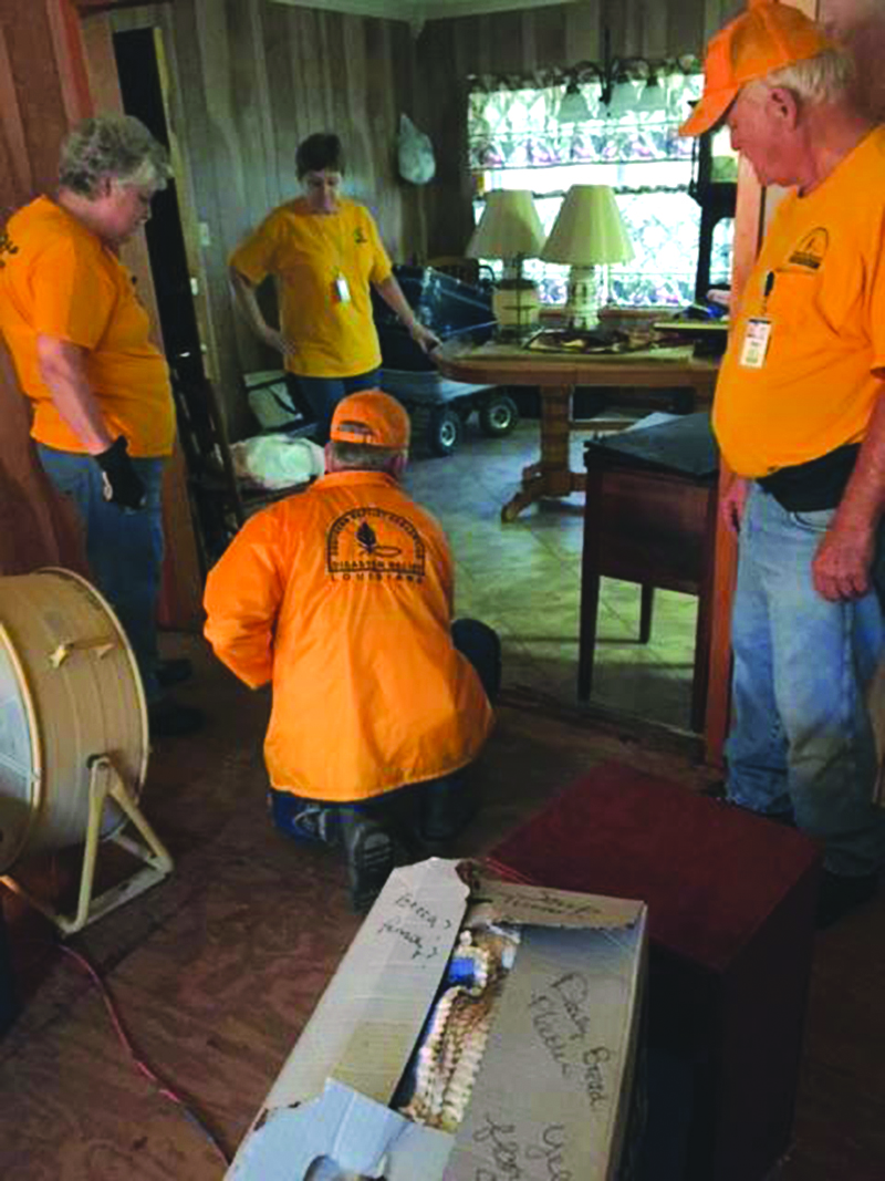 A disaster relief unit from Kentucky assists a homeowner by pulling out carpet damaged by the floodwaters.