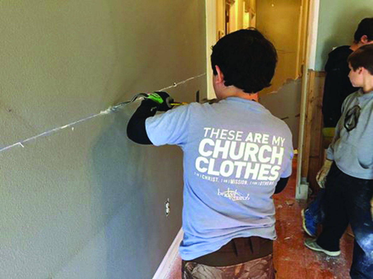 A member of Bridge Church in Madisonville removes dry wall from a Covington home.