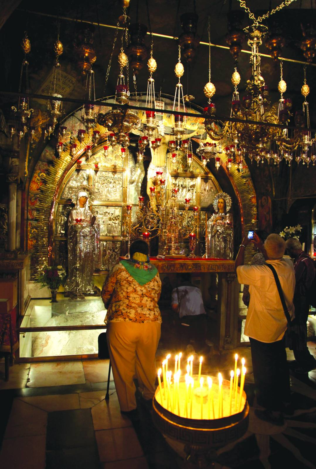 """Visitors to the Church of the Holy Sepulchre look on as one pilgrim stoops down to touch the stone indention the church tradition identifies as the socket where Jesus' cross was placed. Just left of the altar a portion of the presumed """"Calvary"""" hill is visible. Photo by Gar D. Myers"""