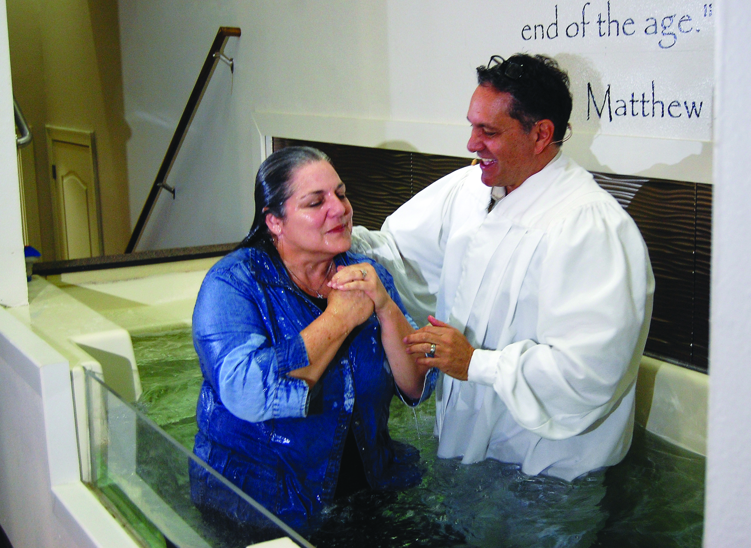 Elizabeth Hill rises up from baptism by Rev. Tom Shepard at the Church of Addis on Feb. 21. photo by mark h hunter