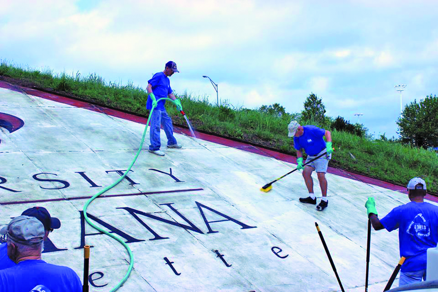 (Top photo) A team from First Baptist Lafayette cleans a sign that motorists see while traveling along I-10 in the city.