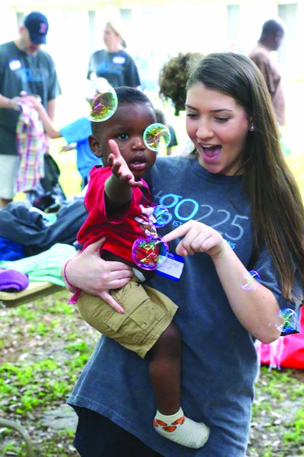 A member of Istrouma Baptist holds a child, as they both try to pop bubbles during the church's Go Day. The one-day effort involved more than 1,000 people from the church, who took a short-term local 'mission trip' on April 17.