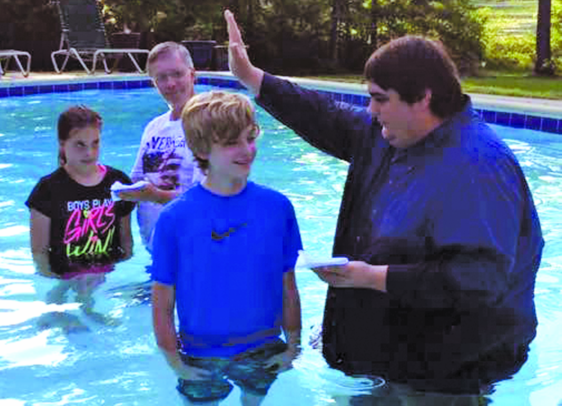 Longstraw Baptist Church Youth Minister Connor Evans (far right) prepares to baptize a youngster during a special baptism service inside a pool. Pastor Larry Emory looks on, as he baptizes a youth as well.