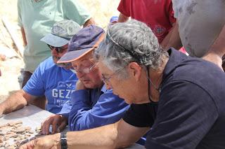Dr. Cole, Eli Yannai and Tsvika Tsuk read pottery during the Gezer dig.