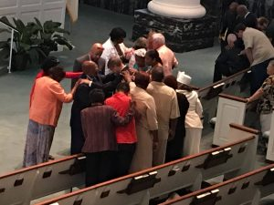 A group of people pray for Oren Conner, pastor of First Baptist Church in Baton Rouge. The church hosted a solemn prayer assembly on July 24, 2016. Dana Truitt photo