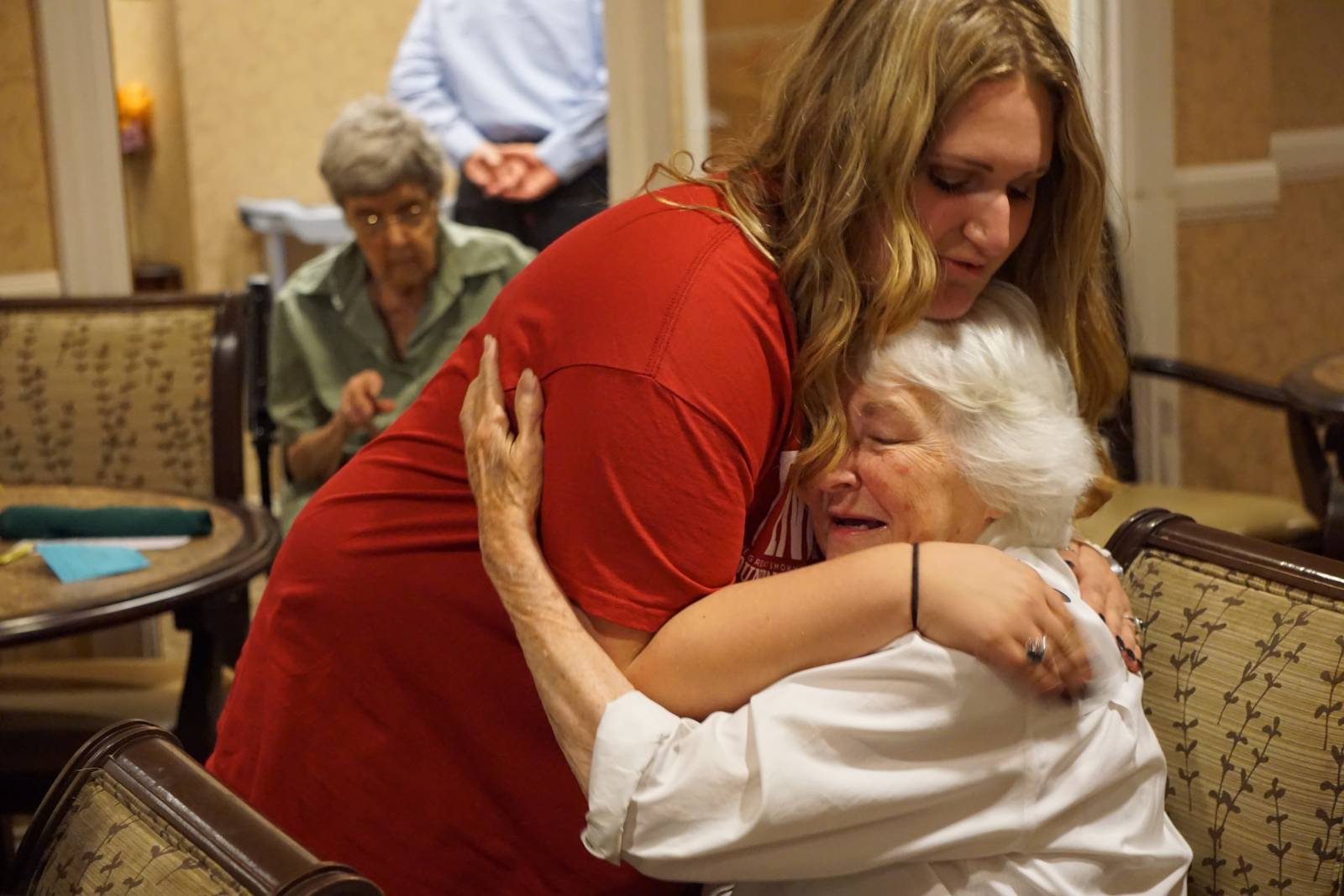 A member of the LABSYC gives an elderly woman a hug after singing at a Tennessee nursing home.