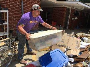 Lance Hukins, a volunteer whose sister-in-law worked at the church daycare that is now closed because of damage from the mid-August floodwaters, helps clear debris scattered throughout the parking lot of Don Avenue Baptist Church.