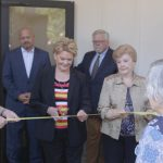 Kay Kirkpatrick cuts the ribbon during the dedication ceremony of the Georgia Barnette Conference Center. Looking on are two co-chair persons of GBCC steering committee Linda David (left) and Glenda Hofius.