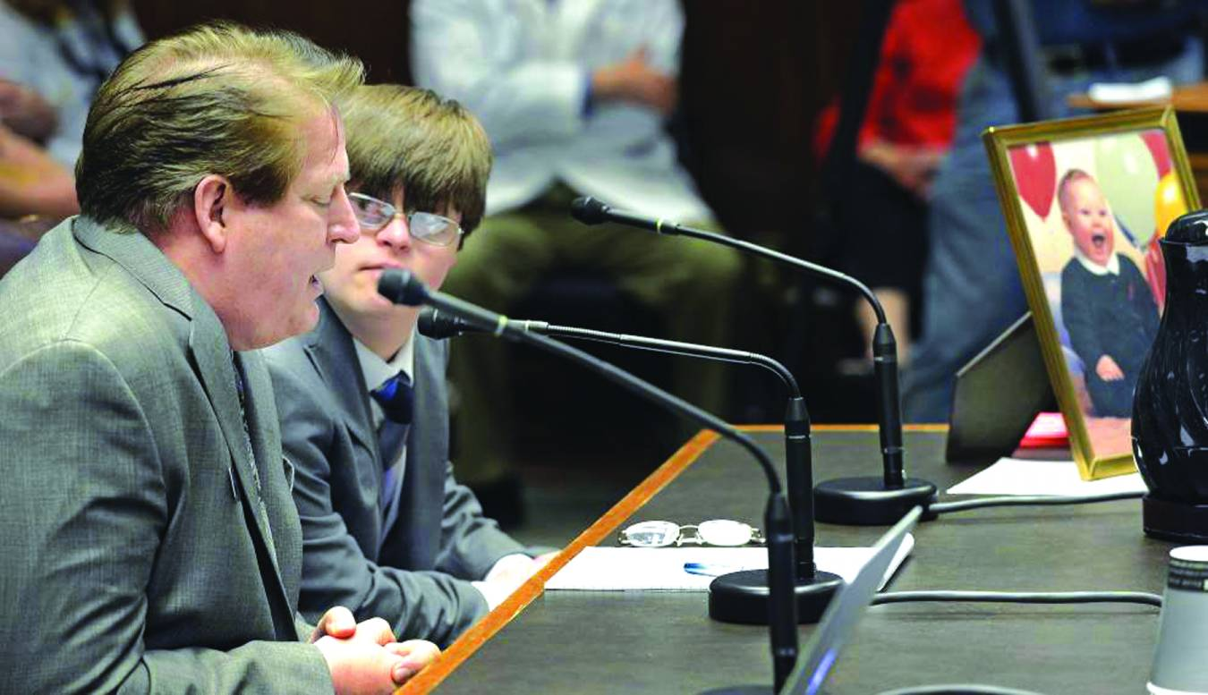 Will Hall, Office of Public Policy Director for the Louisiana Baptist Convention, testifies for Rick Edmond's HB 1019, known as Jacob's Law, concerning abortion in the House Health and Welfare committee while his son Jacob, who has Down's syndrome, looks on. The law, which passed, would protect unborn children, such as Jacob, from being targeted for abortion because of the diagnosis of a condition.